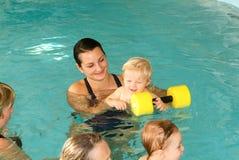 Прелестный младенец наслаждаясь плавать в бассейне с его матерью стоковое изображение rf