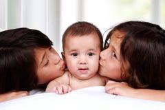 Прелестный младенец расцелованный его братьями Стоковое Изображение