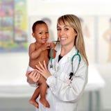 Прелестный младенец с его педиатром стоковые изображения