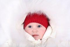 Прелестный ребёнок нося красную шляпу и белый клобук меха Стоковое фото RF