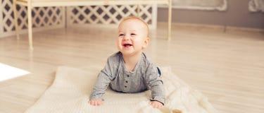 Прелестный смеясь над ребёнок в солнечной спальне Новорожденный ребенок ослабляя Питомник для маленьких ребеят Утро семьи дома стоковая фотография rf