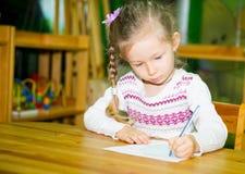 Прелестный чертеж девушки ребенка с красочными карандашами в комнате питомника Ребенк в детском саде в классе preschool Montessor Стоковое Изображение
