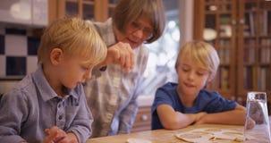 2 прелестных белых дет делая печенья с бабушкой Стоковые Изображения