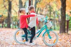 2 прелестных девушки в парке на теплом солнечном дне осени Дети на велосипеде совместно Стоковые Фото