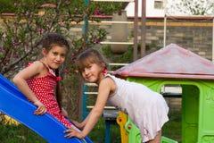 2 прелестных девушки имея потеху на спортивной площадке Стоковое Изображение