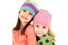 2 прелестных девушки нося обнимать шляп зимы Стоковое Изображение