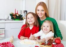 2 прелестных девушки с печеньями рождества выпечки матери в k Стоковая Фотография RF