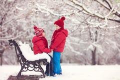 2 прелестных дет, братья мальчика, играя в снежном парке, ho Стоковые Фото