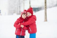 2 прелестных дет, братья мальчика, играя в снежном парке, ho Стоковая Фотография RF