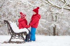 2 прелестных дет, братья мальчика, играя в снежном парке, ho Стоковое Фото