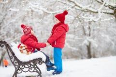 2 прелестных дет, братья мальчика, играя в снежном парке, ho Стоковое Изображение RF