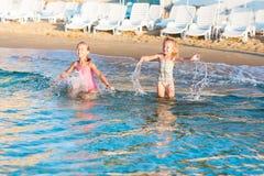 2 прелестных дет играя в море на пляже Стоковое Изображение