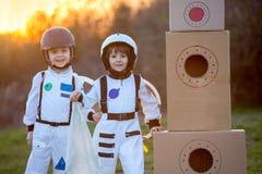 2 прелестных дет, играя в парке на заходе солнца, одели как a Стоковые Фотографии RF