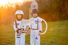 2 прелестных дет, играя в парке на заходе солнца, одели как a Стоковые Изображения RF