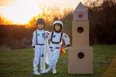 2 прелестных дет, играя в парке на заходе солнца, одели как a Стоковые Фото