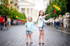 2 прелестных маленьких сестры держа Lithuanian сигнализируют в Вильнюсе Стоковое фото RF