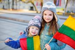 2 прелестных маленьких сестры держа Lithuanian сигнализируют в Вильнюсе Стоковая Фотография