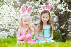 2 прелестных маленьких сестры есть красочные конфеты камеди на пасхе Стоковые Изображения RF