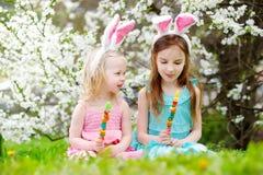 2 прелестных маленьких сестры есть красочные конфеты камеди на пасхе Стоковое фото RF