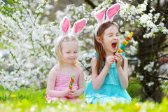2 прелестных маленьких сестры есть красочные конфеты камеди на пасхе Стоковая Фотография RF