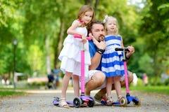 2 прелестных маленьких сестры ехать их самокаты в парке лета Стоковое Фото