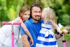 2 прелестных маленьких сестры ехать их самокаты в парке лета Стоковое Изображение