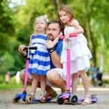 2 прелестных маленьких сестры ехать их самокаты в парке лета Стоковое фото RF