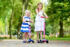 2 прелестных маленьких сестры ехать их самокаты в парке лета Стоковая Фотография RF