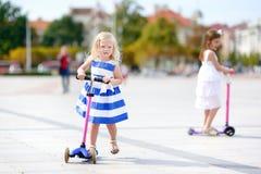2 прелестных маленьких сестры ехать их самокаты в парке лета Стоковые Изображения RF