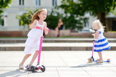 2 прелестных маленьких сестры ехать их самокаты в парке лета Стоковое Изображение RF
