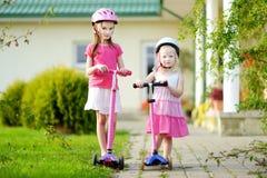 2 прелестных маленьких сестры ехать их самокаты Стоковое фото RF