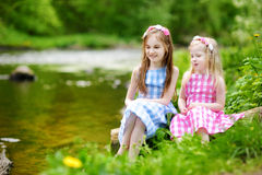 2 прелестных маленьких сестры играя рекой в солнечном парке Стоковое Изображение