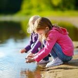 2 прелестных маленьких сестры играя рекой Стоковые Фото