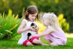 2 прелестных маленьких сестры играя с малыми newborn котятами Стоковые Фото