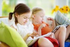 2 прелестных маленьких сестры играя с цифровой таблеткой Стоковая Фотография RF