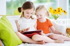 2 прелестных маленьких сестры играя с цифровой таблеткой Стоковое Изображение