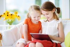 2 прелестных маленьких сестры играя с цифровой таблеткой Стоковые Фото