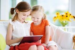 2 прелестных маленьких сестры играя с цифровой таблеткой Стоковые Изображения RF