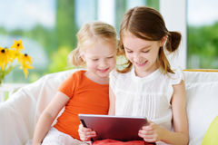 2 прелестных маленьких сестры играя с цифровой таблеткой Стоковое фото RF