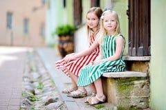2 прелестных маленьких сестры имея потеху на известной улице Literatu в Вильнюсе Стоковое Фото