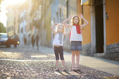 2 прелестных маленьких сестры имея потеху совместно на теплом и солнечном вечере лета в городке Desenzano del Garda Стоковая Фотография RF
