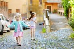 2 прелестных маленьких сестры имея потеху совместно на теплый и солнечный летний день Стоковые Изображения RF