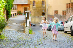 2 прелестных маленьких сестры имея потеху совместно на теплый и солнечный летний день Стоковое фото RF