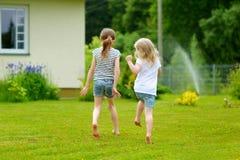 2 прелестных маленьких сестры имея потеху outdoors Стоковые Изображения