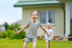 2 прелестных маленьких сестры имея потеху outdoors Стоковая Фотография RF