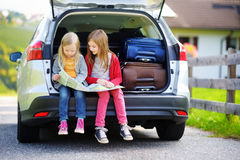 2 прелестных маленьких сестры исследуя карту перед идти на каникулы с их родителями Стоковые Фотографии RF