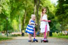 2 прелестных маленьких сестры нося красивые платья ехать их самокаты Стоковая Фотография