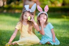 2 прелестных маленьких сестры нося уши зайчика на день пасхи outdoors Стоковые Изображения
