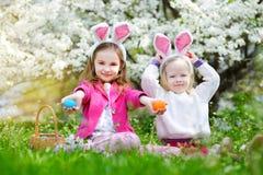 2 прелестных маленьких сестры охотясь для пасхального яйца в зацветая весне садовничают Стоковое фото RF