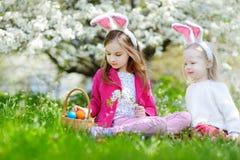 2 прелестных маленьких сестры охотясь для пасхального яйца в зацветая весне садовничают Стоковое Фото